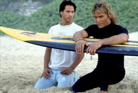 """Cena do filme """"Caçadores de Emoção"""" com Keanu Reeves e Patrick Swayze sentados na praia com uma prancha de surf"""