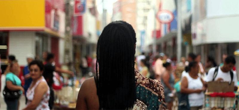 cena do documentário Mwany. Mulher negra de costas olhando para uma cidade