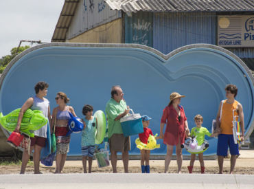 """Foto divulgação filme """"Benzinho"""". Família reunida com roupas de clube e boias."""