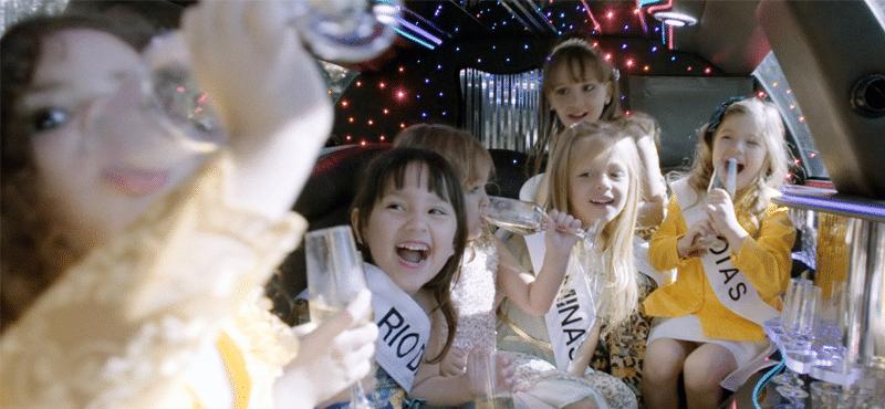 """cena do filme """"mini miss"""" com várias criançar bebendo champanhe em uma limousine"""