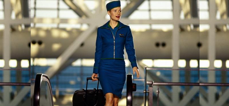 Motivacional - mulher com uniforme de comissária de bordo, saindod e uma escada rolante de um aeroporto com uma mala