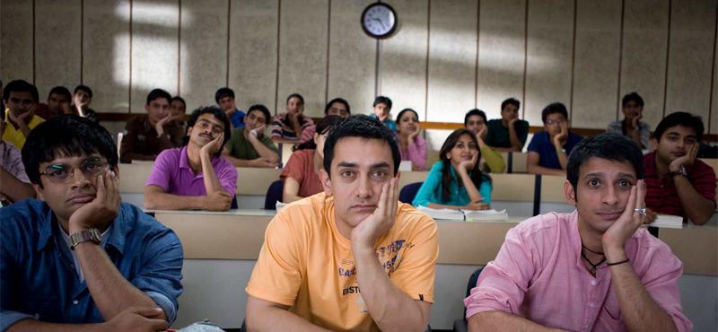 """cena do filme indiano """"três idiotas"""". jovens em sala de aula de uma universidade, todos com a mão no queixo. Sendo três na frente em destaque."""