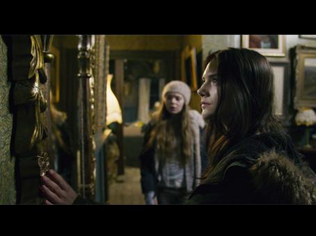 """cena do filme """"a casa do medo"""". Duas meninas olhando para um espelho dentro de uma casa antiga"""