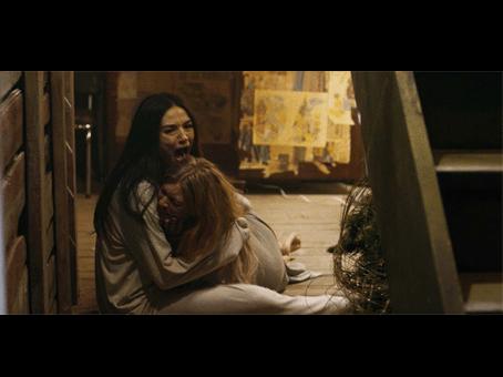 """Cena do filme """"a casa do medo"""". Duas meninas se abraçando e gritando assustadas."""