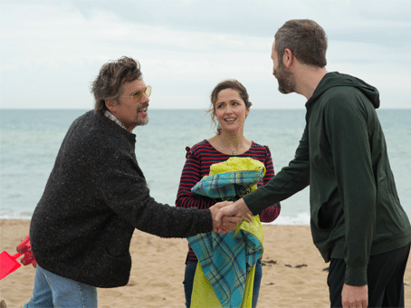 Cena do filme juliet nua e crua, uma mulher na praia com dois homens se cumprimentando